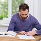 Man som hemma arbetar på skrivbordsarbete Arkivbild