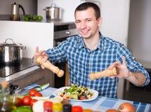 Man som hemma förbereder sallad i kök arkivfoto