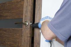 Man som hemma gör reparationer Fixa nyckelhålet i rummet, genom att använda den elektriska skruvmejseln royaltyfri fotografi
