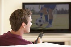 Man som hemma håller ögonen på Widescreen TV Fotografering för Bildbyråer