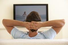 Man som hemma håller ögonen på Widescreen TV Arkivfoton