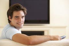 Man som hemma håller ögonen på Widescreen TV Arkivbilder