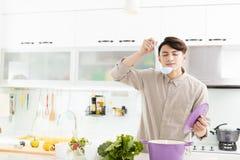 Man som hemma lagar mat i kök royaltyfri fotografi
