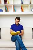 Man som hemma läser den intressanta boken Royaltyfri Fotografi