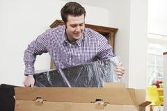 Man som hemma packar upp ny television Royaltyfria Bilder