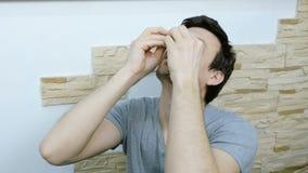 Man som hemma rotera en rastlös människaspinnare Vridningar på näsan 4K arkivfilmer