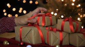 Man som hemma sätter julgåvaaskar med bokehljusbakgrund