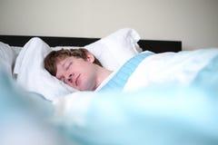 Man som hemma sover i säng Arkivfoton