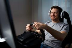 Man som hemma spelar videospelet för springa för bil Arkivfoton