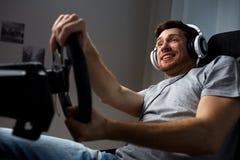 Man som hemma spelar videospelet för springa för bil Royaltyfri Fotografi