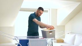 Man som hemma tar tvätterit från uttorkningkuggen stock video