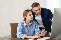 Man som hjälper hans kollegaarbete med datoren arkivfoto