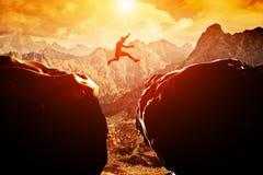 Man som hoppar över klippbrants- mellan två berg