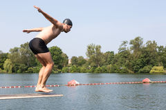 Man som hoppar av dykningbräde på simbassängen Arkivbilder