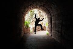 Man som hoppar i en mörk tunnel arkivfoto