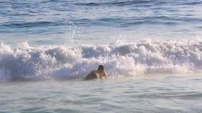 Man som hoppar i stora vågor på stranden i Leblon stock video