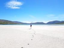 Man som hoppar på en vit sandig strand royaltyfria foton