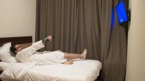 Man som hoppar på säng och strömbrytare TV-kanal med fjärrkontrollen arkivfilmer