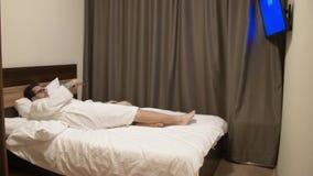 Man som hoppar på säng och strömbrytare TV-kanal med fjärrkontrollen lager videofilmer