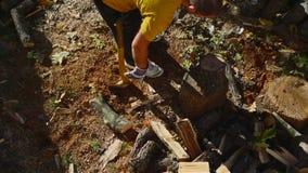 Man som hugger av trä med en yxa lager videofilmer