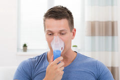 Man som inhalerar till och med inhalatormaskering Arkivbild