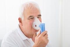 Man som inhalerar till och med syremaskering royaltyfri bild