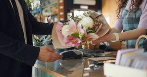 Man som inhandlar blommor som betalar med kassa i blomsterhandlares lager som ger pengar lager videofilmer