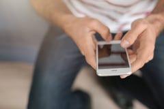 Man som inomhus använder mobiltelefonen, royaltyfri bild