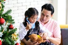 Man som inomhus döljer gåvan för föräldern och det lilla barnet som har gyckel nära julgranen bak hans baksida royaltyfri bild