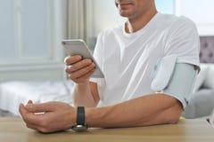 Man som inomhus kontrollerar blodtryck med den moderna bildskärmen och smartphonen på tabellen, closeup royaltyfria foton