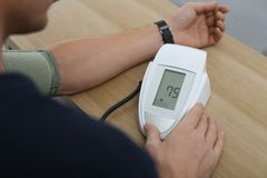 Man som inomhus kontrollerar blodtryck med sphygmomanometeren på tabellen, closeup arkivfoton