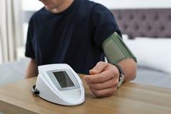 Man som inomhus kontrollerar blodtryck med sphygmomanometeren på tabellen, closeup royaltyfri bild