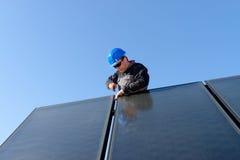 Man som installerar alternativ photovolta för sol- energi Arkivbild