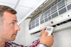 Man som installerar den betingande enheten för ny luft Arkivbild