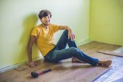 Man som installerar den nya trälaminatdurken infraröd golvvärme arkivbild