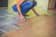Man som installerar den nya trälaminatdurken infraröd golvvärme royaltyfri bild