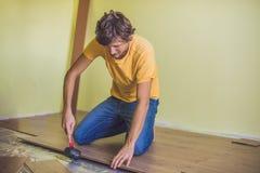 Man som installerar den nya trälaminatdurken infraröd golvvärme royaltyfri fotografi