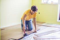 Man som installerar den nya trälaminatdurken infraröd golvvärme fotografering för bildbyråer