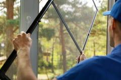 Man som installerar myggnättrådingreppet på husfönster royaltyfri bild