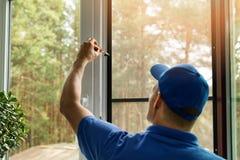 Man som installerar myggnättrådskärmen på husfönster royaltyfri bild