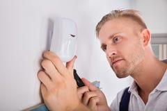 Man som installerar rörelseavkännaren för säkerhetssystem arkivfoto