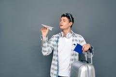 Man som isoleras på grått anseende för väggturismbegrepp med resväskainnehavpasset med biljetten och framställning av flugaorigam arkivbilder