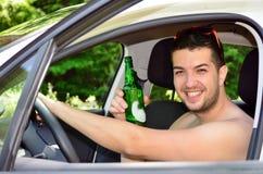Man som kör bilen med öl i hand Royaltyfri Fotografi