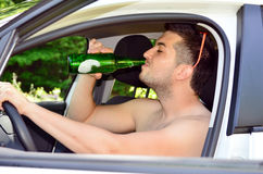 Man som kör bilen med öl i hand Arkivbilder