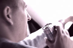 Man som kör en bil som dricker den aktiverande drinken Royaltyfri Bild