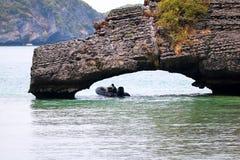 Man som kör ett fartyg under en sten Fotografering för Bildbyråer
