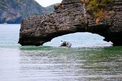 Man som kör ett fartyg under en sten Royaltyfri Foto