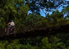 Man som kör ridning över den gamla bron i guatemalanska berg royaltyfri bild