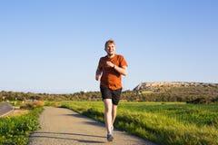 Man som kör utomhus- sprinta för framgång Den manliga idrottsman nen för konditionlöparesporten sprintar in på stor hastighet i h Royaltyfri Bild