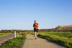 Man som kör utomhus- sprinta för framgång Den manliga idrottsman nen för konditionlöparesporten sprintar in på stor hastighet i h Arkivfoton